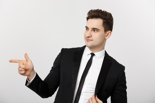비즈니스 개념: 세로 잘생긴 젊은 사업가가 빈 카피 공간 옆에 손가락을 가리킵니다. 흰색 배경 위에 절연 광고 제품의 개념