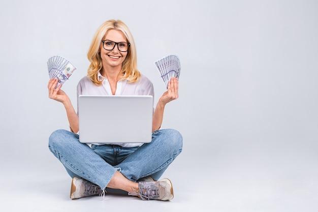 ビジネスコンセプト。蓮華座の床に座って、白い背景で隔離のラップトップと紙幣を保持しているカジュアルな高齢の女性の肖像画。テキスト用のスペースをコピーします。