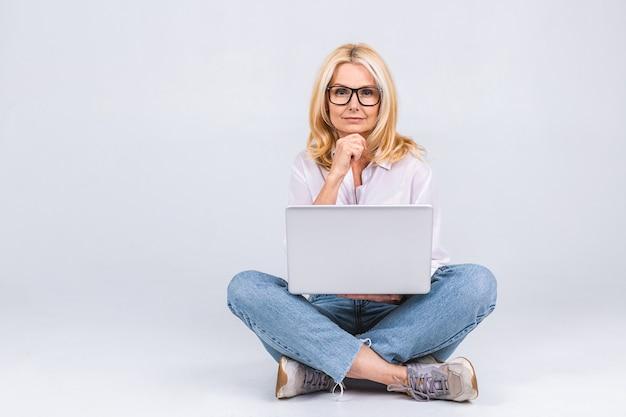 ビジネスコンセプト。蓮の位置で床に座って、白い背景で隔離のラップトップを保持しているカジュアルな高齢の女性の肖像画。テキスト用のスペースをコピーします。