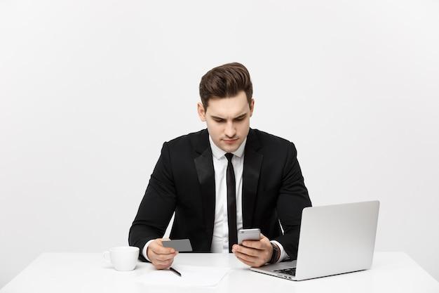 비즈니스 개념: 노트북 컴퓨터와 직불 카드를 들고 있는 휴대 전화를 사용하는 젊은 사업가의 초상화. 회색 배경 위에 격리.