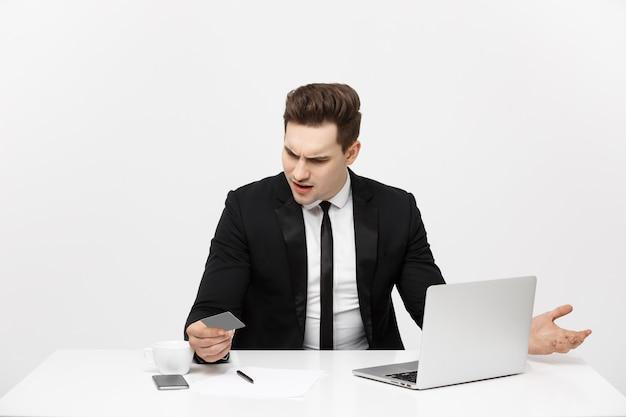 ラップトップコンピューターとデビットカードを保持している携帯電話を使用して青年実業家のビジネスコンセプトの肖像画...