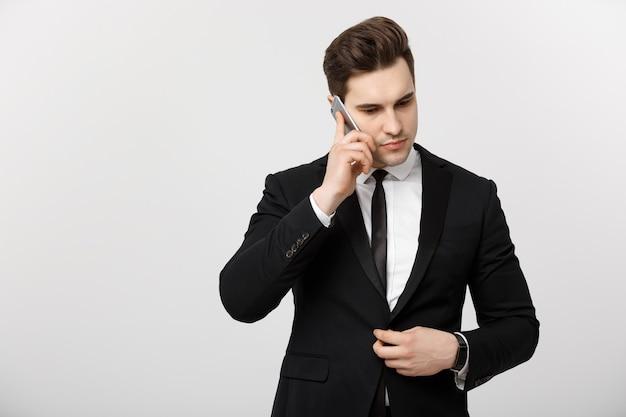 비즈니스 개념: 진지하고 스트레스를 받는 표정으로 휴대전화로 통화하는 젊고 잘생긴 사업가의 초상화. 흰색 배경 위에 격리.