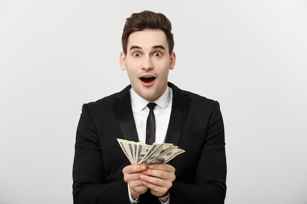 Concetto di affari: ritratto dell'uomo d'affari scioccato che mostra un sacco di soldi isolati su sfondo bianco.