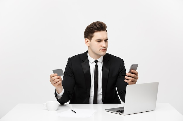 Business concept portrait of young businessman using laptop computer and mobile phone holding debit ...