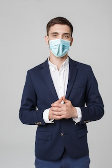 Business concept - portrait young successful businessman in face mask osing over dark wall. copy space.