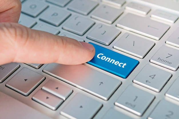 Business concept shows as well as the fingers that press submit on the keyboard laptop. connect inscriptions on the grey silver keyboard button close up.