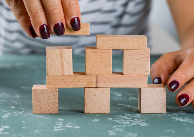 Business concept side view. woman building up tower from wooden blocks.