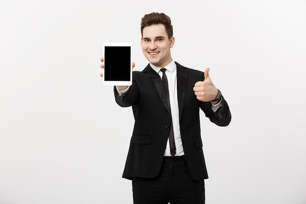 ビジネスコンセプト:灰色のスタジオの背景の上に親指を示すタブレットと笑顔のビジネスマン