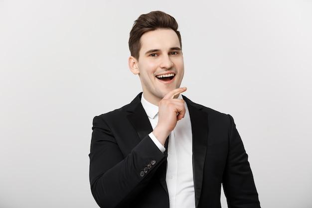 白い孤立した背景の上に立って、感動的な思いやりのあるハンサムな男を笑顔のビジネスコンセプト...