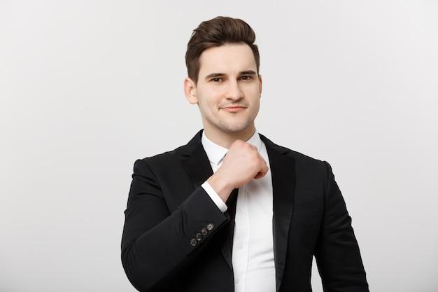 Concetto di affari: uomo bello premuroso sorridente in piedi su sfondo bianco isolato e toccando il mento con la mano