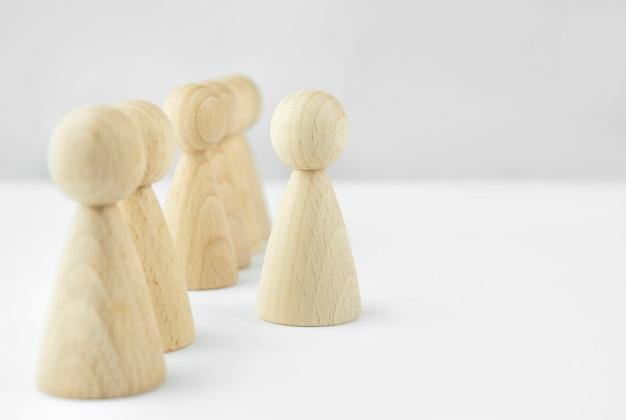 사업 개념. 직원 모집. 헤드헌팅. 많은 직원. 가벼운 테이블에 나무 작은 남자. 공간을 복사하십시오. 프리미엄 사진