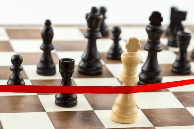 Бизнес-концепция - стратегия, конкуренция, лидерство, вызов. фигура короля пересекает красную финишную ленту