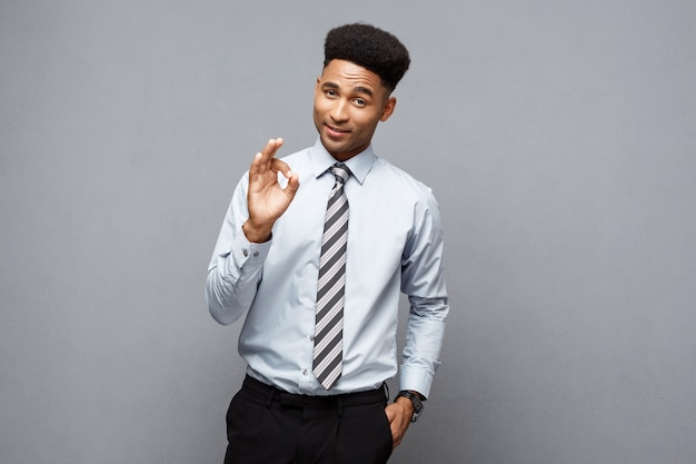 Business concept - successful african american businessman showing ok finger sign in front of him.