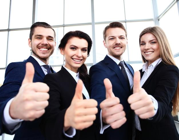 Бизнес-концепция - успешные молодые деловые люди показывают палец вверх