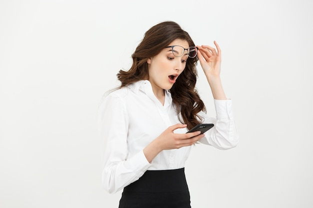 Business concept surprised young woman holding mobile phone and staring at it