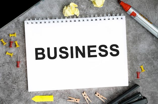 Текст бизнес-концепции на белом блокноте с булавками, маркером и степлером на бетонном столе