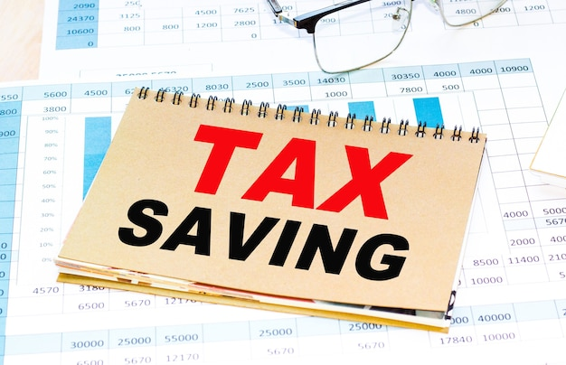 Бизнес-концепция. текст налоговая экономия лист бумаги для заметок, карандаши на заднем плане