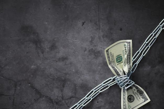 비즈니스 개념입니다. 국가 통화의 가치 하락. 100달러 지폐입니다. 인플레이션과 침체. 측정 사슬로 100달러 지폐를 조입니다.