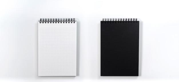 ビジネスコンセプト-モックアップのための白い背景の机の上の黒いノートブックのトップビューコレクション