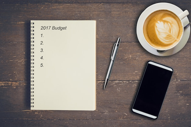 Концепция бизнеса. бюджет 2017 для ноутбуков с записью сверху, ручкой, чашкой кофе и телефоном на деревянном столе.