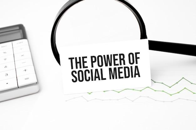 ビジネスコンセプト。電卓、拡大鏡、ペン、卓上時計、ノートブックの木製の背景に書かれた例の上面図。ソーシャルメディアの力