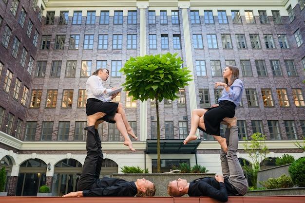 두 명의 기본 남성 파트너의 아크로요가 요소가 있는 비즈니스 개념은 여성 전단지를 발로 들고, 소녀들은 말하고 메모하고, 사무실 옷을 입습니다.