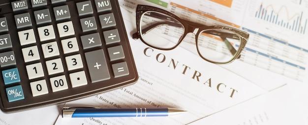 Бизнес-концепция с очками калькулятора и карандашом на документах. деловые графики и диаграммы. договор