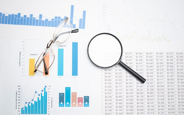 Business concept with calculator glasses pencil and magnifying glass on documents. business grafs and charts
