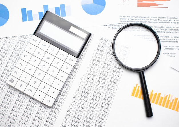 Business concept with calculator and magnifying glass on documents