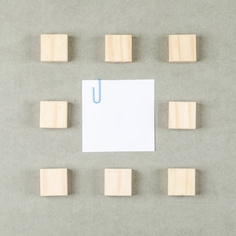 Business concept with clipped sticky note, wooden blocks on grey surface flat lay.