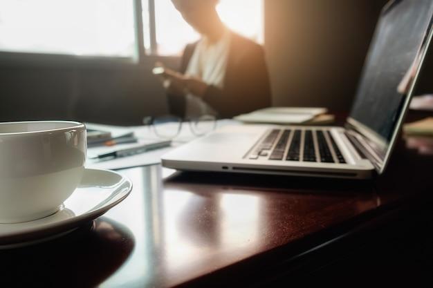 Concetto di affari con spazio di copia. tavolo da ufficio con penna e diagramma di analisi, computer, taccuino, tazza di caffè sullo scrittorio. tono di vernice retro filtro, messa a fuoco selettiva.