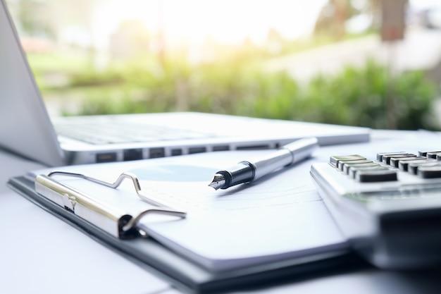 Бизнес-концепция с копией пространства. стол офисного стола с фокусом пера и диаграммой анализа, компьютер, блокнот, чашка кофе на столе. старинный тон ретро-фильтр, избирательный фокус.