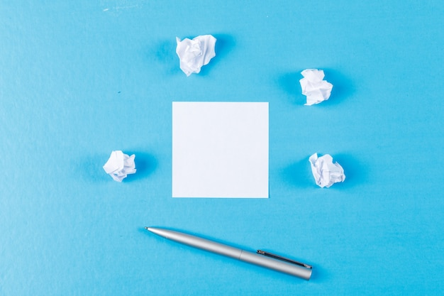 Business concept with crumpled paper wads, sticky note, pen on blue background flat lay.