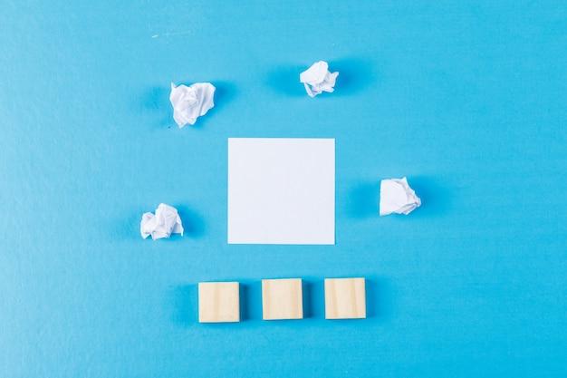 しわくちゃの紙の塊、付箋、平らな青色の背景に木製キューブのビジネスコンセプトを置きます。
