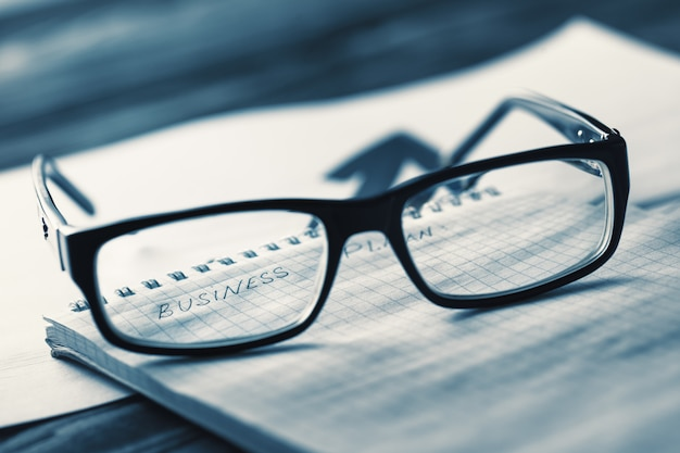 Business concept with glasses and a business plan