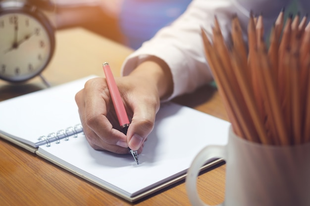 Business concept with hand holding pen while writing on notebook