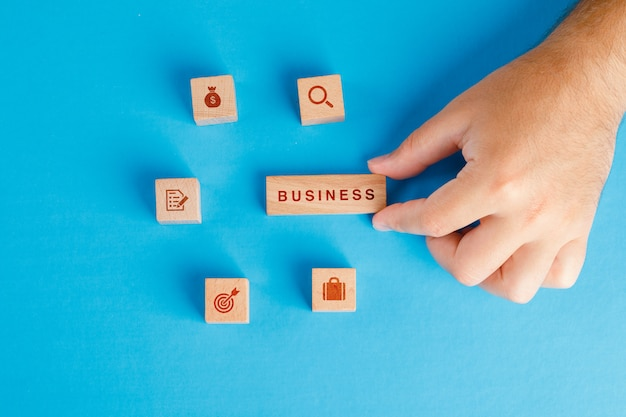 Business concept with icons on wooden cubes on blue table flat lay. hand holding wooden block.
