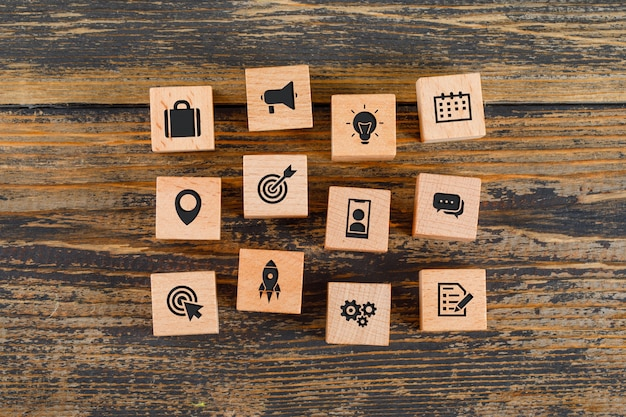 Business concept with icons on wooden cubes on wooden table flat lay.