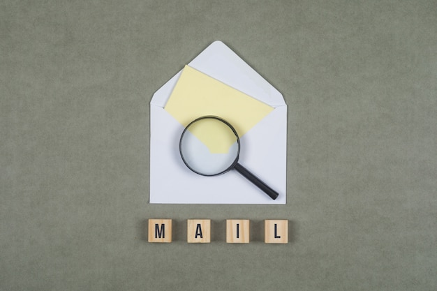 Business concept with letter in envelope, magnifying glass, wood cubes on grey surface flat lay.