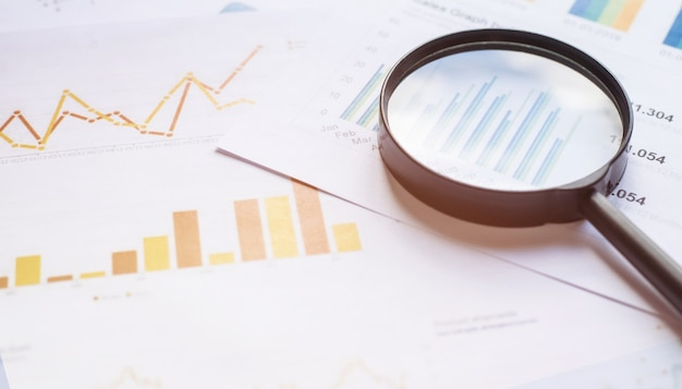 Бизнес-концепция с увеличительным стеклом на документах. деловые графики и диаграммы