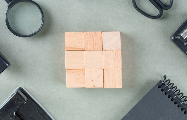 Business concept with wooden blocks, black notebook, magnifying glass top view.
