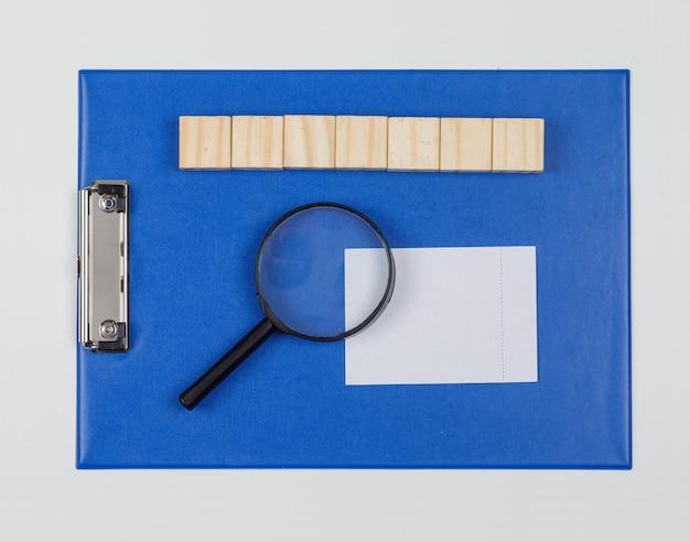 Concetto di affari con i blocchi di legno, elenco di carta, lente d'ingrandimento, nota appiccicosa sulla disposizione piana del fondo bianco.