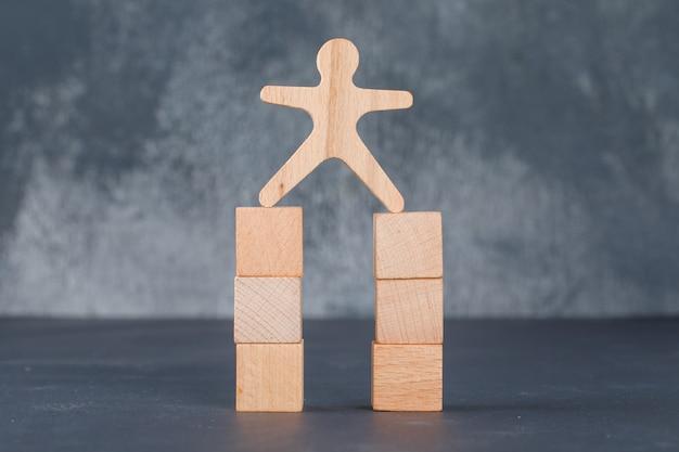 Concetto di affari con blocchi di legno con figura umana in legno.