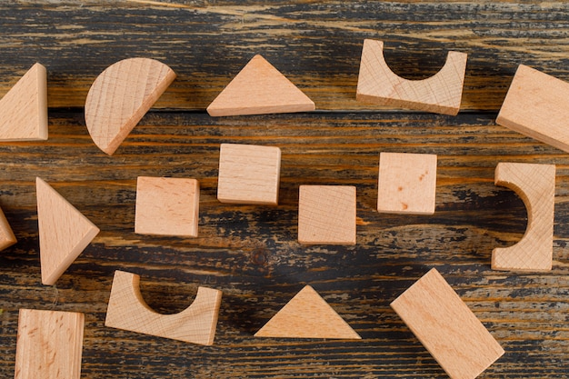 Business concept with wooden geometric shapes on wooden table flat lay.