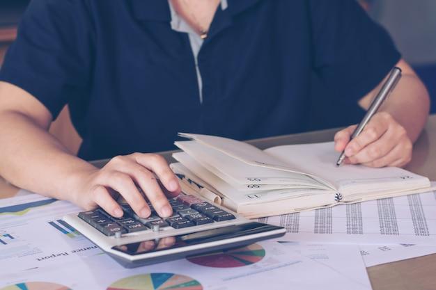 Бизнес-концепция: женщина рука с помощью калькулятора и написание сделать заметку с рассчитать на