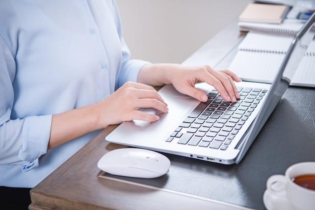 Бизнес-концепция. женщина в синей рубашке, печатающая на компьютере с кофе на офисном столе, подсветка, эффект солнечных бликов, крупный план, вид сбоку, копия пространства