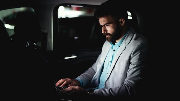 Бизнес-концепция, работающая на ноутбуке, сердитый человек работает допоздна.