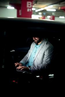 Бизнес-концепция, работающая на ноутбуке, успешный бизнесмен работает поздно, занимаясь серфингом в интернете.