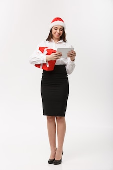 Business concept - young business woman woking on digital tablet in christmas day.
