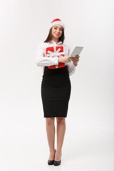 ビジネスコンセプト-クリスマスの日にデジタルタブレットで目覚める若いビジネス女性。